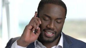 Young black gentleman in jacket, speaking mobile phone